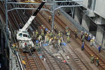 架線用の電柱をクレーン車で撤去しているところ